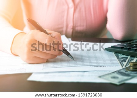 Closeup front view on girl's hand who is holding a pen and doing calculations using documents with tables and a calculator. Calculation of taxes and profits, preparation of accounting reports concept. #1591723030