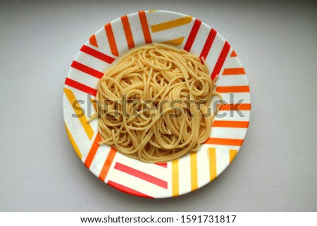 Cooked cooked spaghetti lie in a colorful motley plate #1591731817