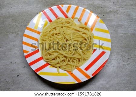 Cooked cooked spaghetti lie in a colorful motley plate #1591731820