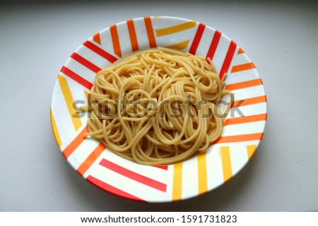 Cooked cooked spaghetti lie in a colorful motley plate #1591731823