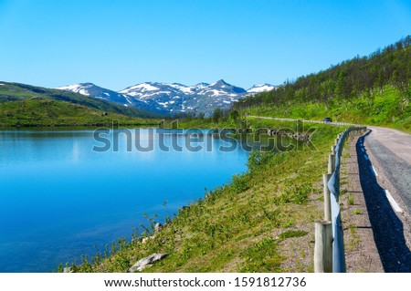 The road to the pass on a sunny morning, the mountains on the right, the lake on the left. Cycling tour in Polar Norway. #1591812736
