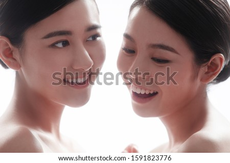 Two young woman isolated on background #1591823776