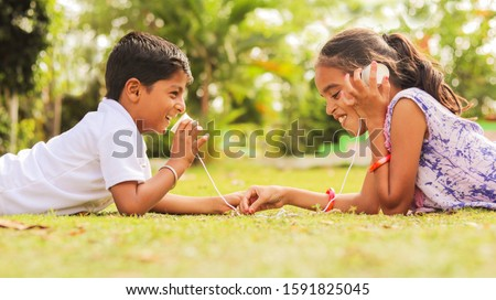 Two children having fun by playing with String Telephone at park during vacation - Concept of brain development and socializing by playing outdoor games in the technology driven world.