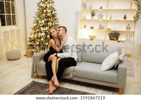 couple in love kisses and hugs on the sofa near the Christmas tree lights. New year's night.Christmas. black dress and white shirt, jewelry #1591867219
