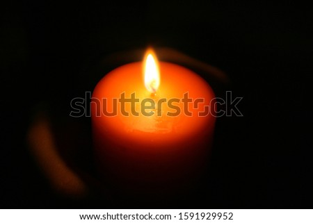 The candle glows in the darkness in the hands #1591929952