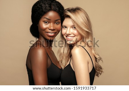 Multi Ethnic Group of Womans with diffrent types of skin  together and looking on camera. Caucasian and African ethnicity womens posing and smiling against beige background. #1591933717