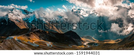 Panoramic Image of Grossglockner Alpine Road. Curvy Winding Road in Alps. Dramatic Sky. Royalty-Free Stock Photo #1591944031