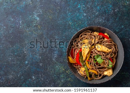Japanese dish buckwheat soba noodles with chicken and vegetables carrot, bell pepper and green beans in grey bowl, top view, copy space. #1591961137