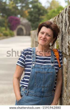 portrait of a brunette woman of mature age smiling and dressed in a cowboy bib #1591962880
