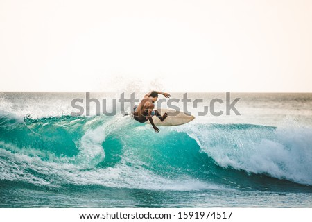 professional surfer riding waves in Bali, Indonesia. men catching waves in ocean, isolated. Surfing action water board sport. people water sport lessons and beach swimming activity on summer vacation #1591974517