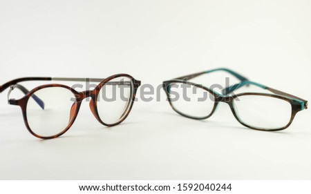 Two pairs of modern glasses isolated in a studio shot one with black and turquoise colored frames and a blue blocking pair prescribed from a profession optometrist with isolated white background  #1592040244