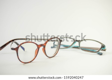 Two pairs of modern glasses isolated in a studio shot one with black and turquoise colored frames and a blue blocking pair prescribed from a profession optometrist with isolated white background  #1592040247