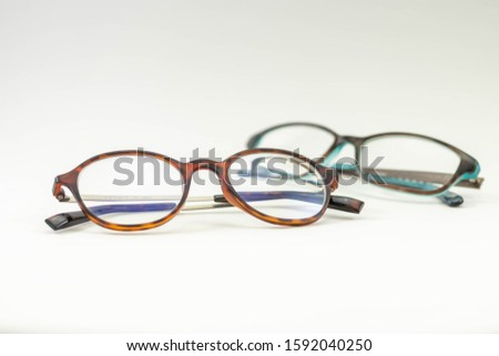 Two pairs of modern glasses isolated in a studio shot one with black and turquoise colored frames and a blue blocking pair prescribed from a profession optometrist with isolated white background  #1592040250