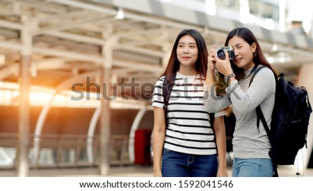 Travellers backpacker teenager female standing at landmark in Bangkok, Thailand and  using camera shooting beautiful place with happiness #1592041546