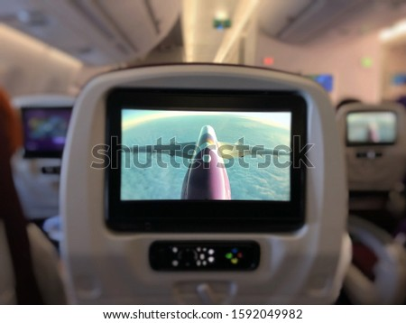 In flight head rest screen showing a picture from flight camera, an airplane is flying above the clouds. Travel is pleasure.