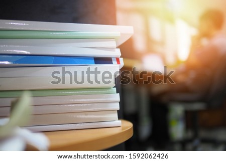 Pile of documents or files in office with the background of business or office staff working on the back, selective focused picture of papers or books on a wooden desk, education or academic concept #1592062426