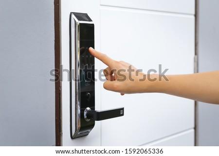Close-up hand pressing keywords to lock and unlock door - Door access control keypad with keycard reader Royalty-Free Stock Photo #1592065336