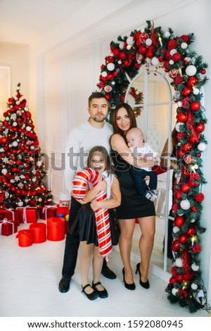 Parents with two children standing before a Christmas tree indoors. Vertical portrait #1592080945