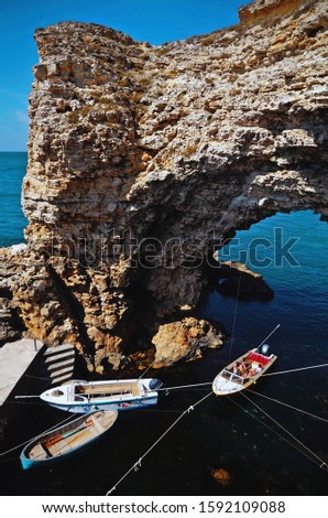 Boats at the pier near a large rocky arch on the Black sea in Big Atlesh (Tarhankut, Crimea).