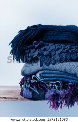 Folded woollen and checkered plaids, scarfs. Winter textile on wooden rustic shelf behand wall. Cozy warm concept #1592131093