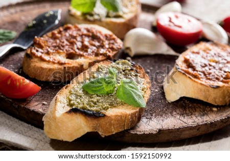 Sliced traditional toast bread with basil pesto and tomato pesto on a cutting board and white wooden table. #1592150992