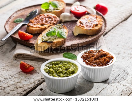 Sliced traditional toast bread with basil pesto and tomato pesto on a cutting board and white wooden table. #1592151001