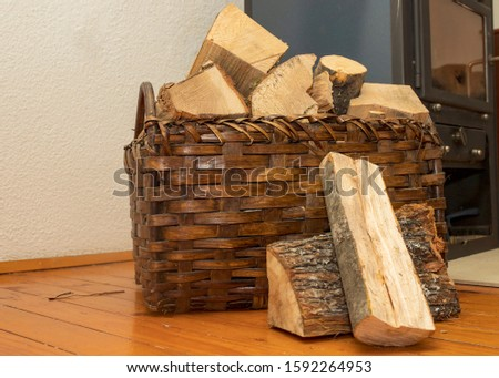 Basket with wood for fireplace and and fireplace in the background #1592264953