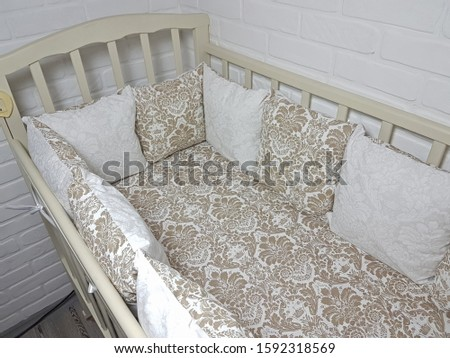 Set of bed linen for the baby. Pillows, blankets, sheets in the crib. The beige and white a flower pattern. Bed in the children's room.  #1592318569