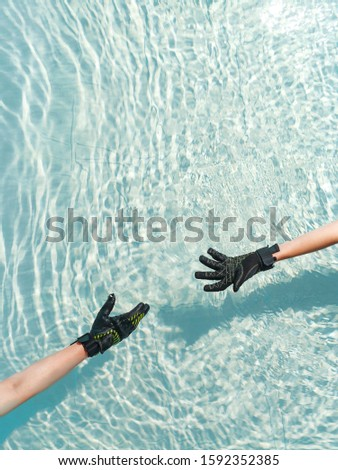 two women's hands in gloves in the water stretch each other to another concept of water sports #1592352385