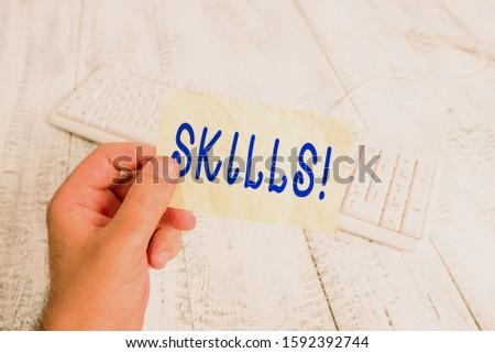 Text sign showing Skills. Conceptual photo ability do something very well by nature man holding colorful reminder square shaped paper white keyboard wood floor. #1592392744