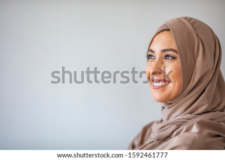 Portrait of pretty young asian muslim woman in head scarf smile. Portrait closeup of muslim prayer woman 20s in hijab smiling isolated over gray background.  #1592461777