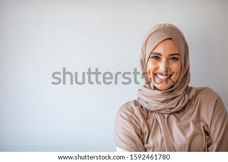 Portrait of pretty young asian muslim woman in head scarf smile. Portrait closeup of muslim prayer woman 20s in hijab smiling isolated over gray background.  #1592461780