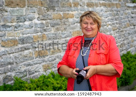 A Mature plump woman in red walks in an ancient castle, smiles and looks at the camera. Tallinn, Estonia #1592487943