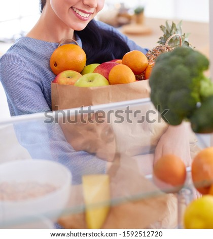 Smiling woman taking a fresh fruit out of the fridge, healthy food concept #1592512720