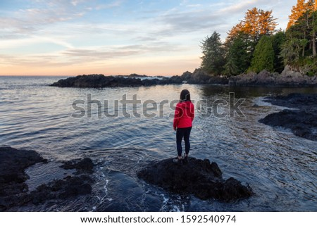 Wild Pacifc Trail, Ucluelet, Vancouver Island, BC, Canada. Adventurous Girl Enjoying the Beautiful View of the Rocky Ocean Coast during a colorful morning sunrise. Concept: Travel, adventure, freedom #1592540974
