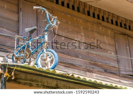 Vintage bicycle On a vintage roof And the background of the vintage wooden house #1592590243