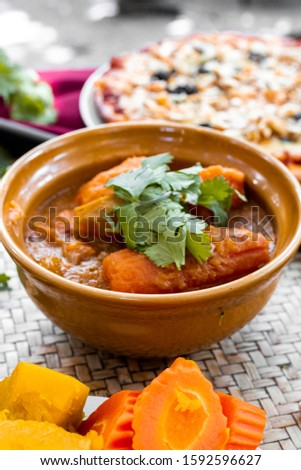 vegetable soup with carrot and pumpking, healthy and vegan on wooden background #1592596627
