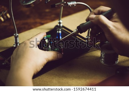 Hands of man holding solder iron  soldering the pin on electronics circuit board,  DIY hobbies and electrician workshop concept. #1592674411