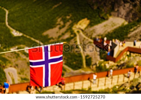 Trollstigen mountain road landscape in Norway, Europe. Norwegian flag waving and many tourists people on viewing platform in background. National tourist route. #1592725270
