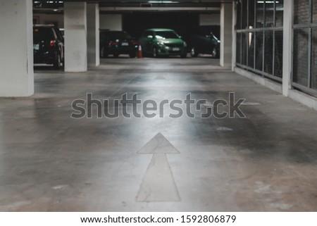 Direction arrow on concrete floor of office parking lots building #1592806879