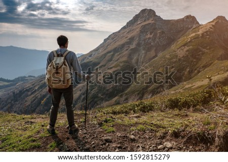Young man standing on top of cliff in summer mountains at sunset and enjoying view of nature. The idea and concept of hiking, photography and travel. Russia, ski resort Rosa Khutor, Rosa Peak
