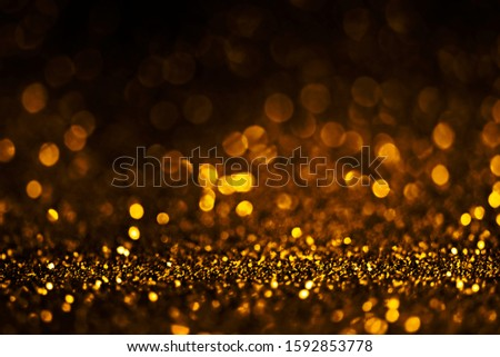 Blur gold light circle background. Sparkling firework bokeh dots on dark wall. Luxury and classy new year and christmas celebration party textured backdrop. Blurry golden dust frame design.