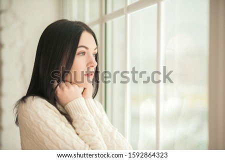 Portrait of a brunette girl at the window with reflection closeup. Young woman in a white knitted dress on a background of a large window and copy space. #1592864323