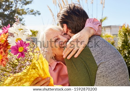 Mother hugs her son and thanks for the flowers on Mother's Day #1592870200