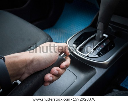 Close up of Male hand pulling a parking brake in car. #1592928370