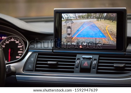 Interior of premium car with rearview camera dynamic trajectory turning lines and parking assistant steering wheel turned right. Driver assistance parking system. Help assist options of luxury car.  #1592947639