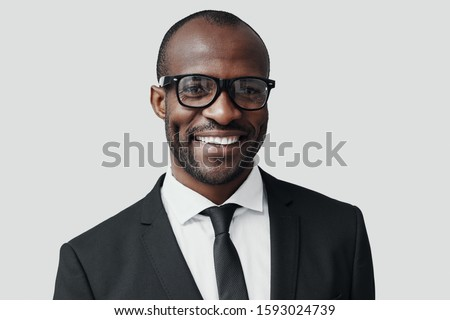 Confident young African man in formalwear looking at camera and smiling while standing against grey background #1593024739