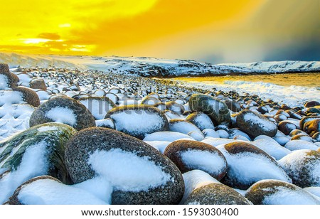 Snow covered beach stones sunset scene. Sunset snow beach landscape. Sunset snowy beach stones view. Snow beach sunset scene #1593030400