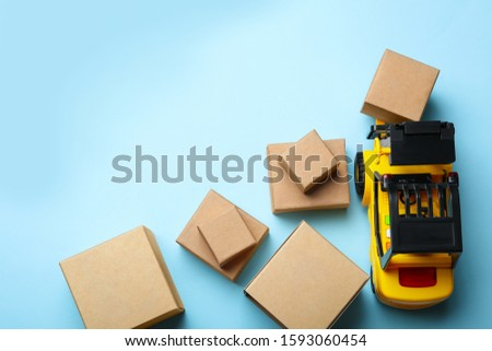 Top view of toy forklift with boxes on blue background, space for text. Logistics and wholesale concept #1593060454