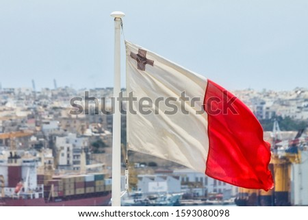 Flag of Malta on flagpole with cityscape in the background. #1593080098